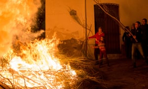 Villagers throw fuel onto a fire in Spain during Antonio Abad festival