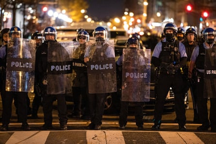 Police stand guard to keep the rival groups apart.