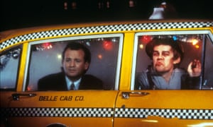 Bill Murray and David Johansen peer out of a New York taxi cab in the film comedy Scrooged.