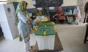An election official seals ballot boxes before people vote at a polling station in Islamabad.