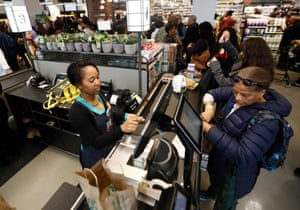 A cashier, left, checks out items as a customer shops during the grand opening of the Whole Foods supermarket in Newark, N.J.
