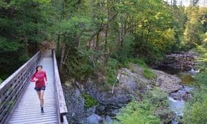 Jen Benson runs across a bridge at Coed y Brenin
