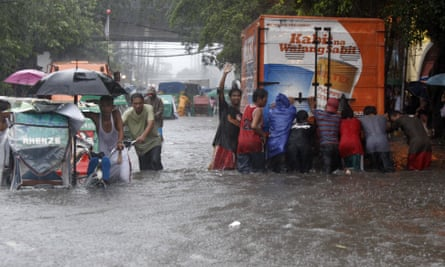 Residents wade through floodwaters in Manila in September 2009, after tropical storm Ketsana slammed into the eastern side of the northern Philippines.