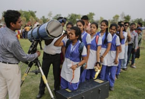Schoolchildren wait to view Mercury through a telescope in Lucknow, India