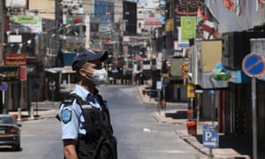 A Palestinian policeman stands guard in an empty street in the West Bank city of Nablus on 3 July 2020