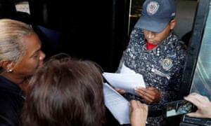 Venezuelan opposition supporters hand documents to a police officer at the presidential residence in Caracas.
