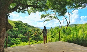 A woman stands on a wooden terrace looking out over forests, to the sea, at the Otentic Mountain eco-retreat, Mauritius.