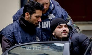 Alessandro Giannelli is bundled into a police car after his arrested as part of a swoop on a mafia clan.