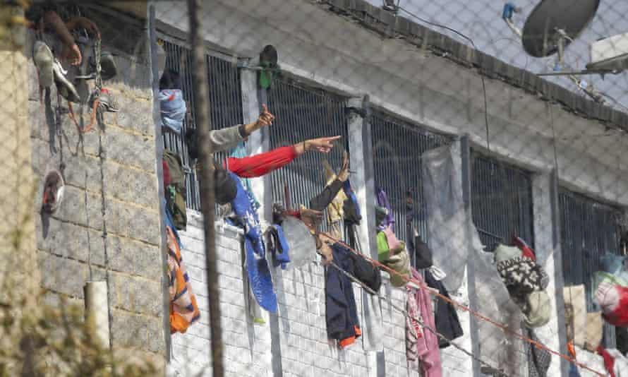 Inmates point from inside La Modelo jail