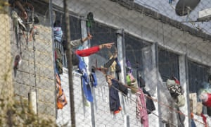 Inmates at La Modelo jail in Bogotá, Colombia, gesticulate from their cell windows