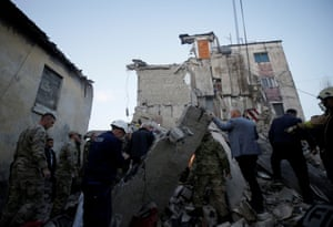 Emergency personnel clearing rubble near a damaged building