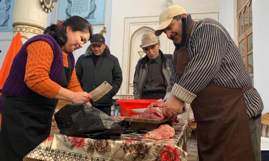 Sofi Asadov and his wife Delfuza prepare fish for a Hanukah celebration.