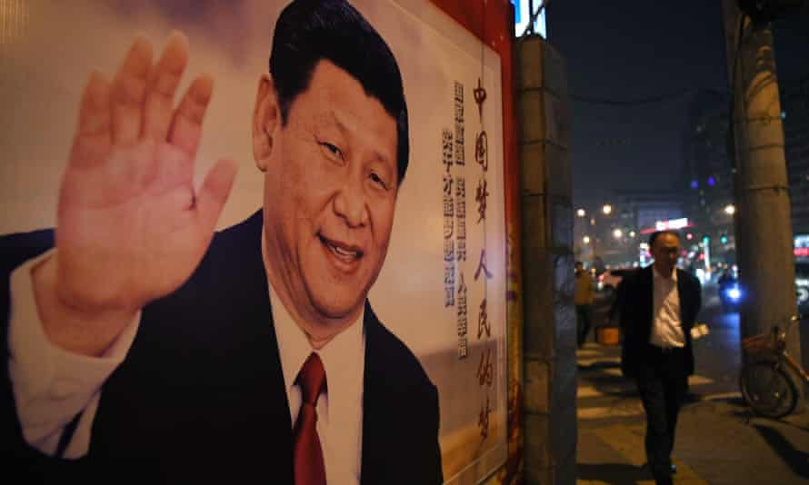 A man walks past a roadside poster of Chinese President Xi Jinping after the closing of the 19th Communist Party Congress in Beijing.