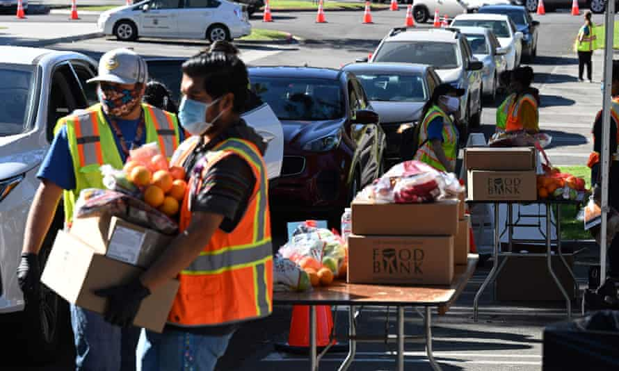 Volunteers at a food bank in Los Angeles help load supplies into people's cars.