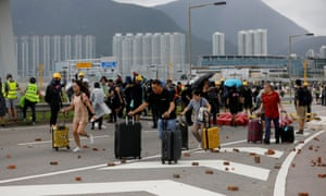 Passengers walk to a terminal as protesters block the roads leading to Hong Kong's international airport