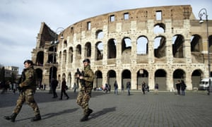 Italian army soldiers patrol the area in front of Rome's Colosseum