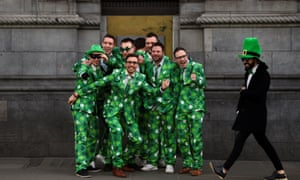 People wearing Shamrock suits queue for an ATM on St. Patrick's Day in Dublin, Ireland, March 17, 2018. REUTERS/Clodagh Kilcoyne