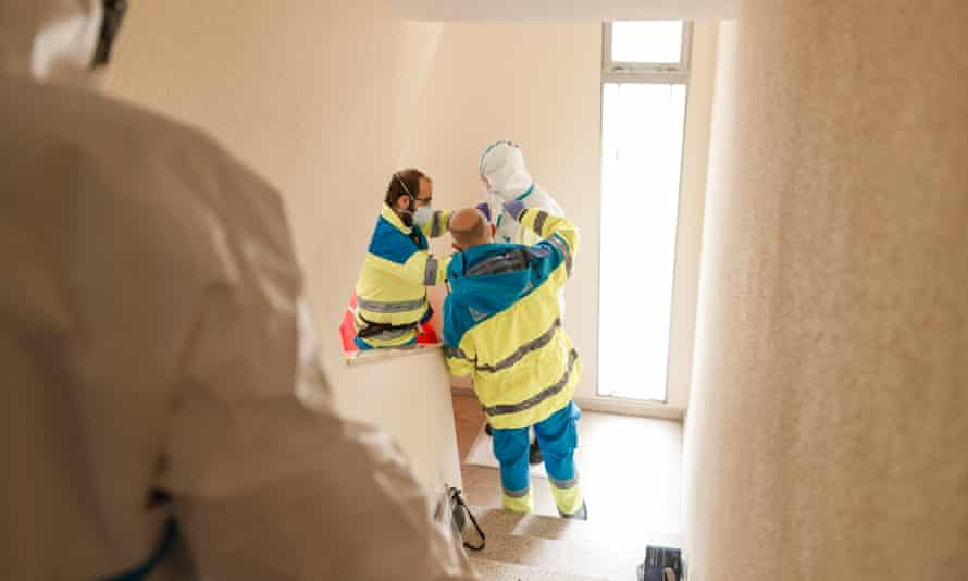 Victor and Miguel, both technicians from the UVI, help Marta, the nurse, to remove the protective suit once the home visit is over.