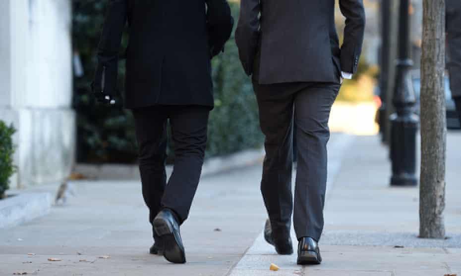two suited men walking away