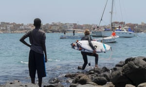 A local boy watches South African surfer Beyrick De Vries head out towards the surf at Ngor, Senegal