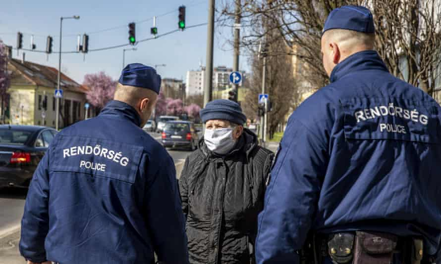 Police officers talk to a woman in Bekescsaba, Hungary on Tuesday.