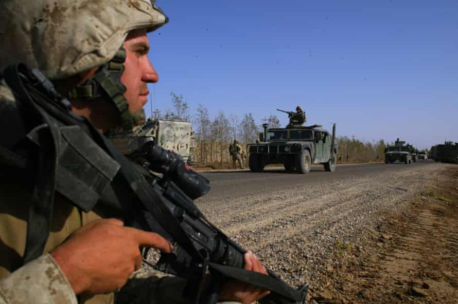 A man holding a machine gun stands by the side of a dirt road on which armoured vehicles are travelling