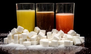 Fizzy drinks behind a pile of sugar cubes