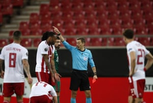 Referee Clement Turpin shows a red card to Olympiakos' Ruben Semedo.