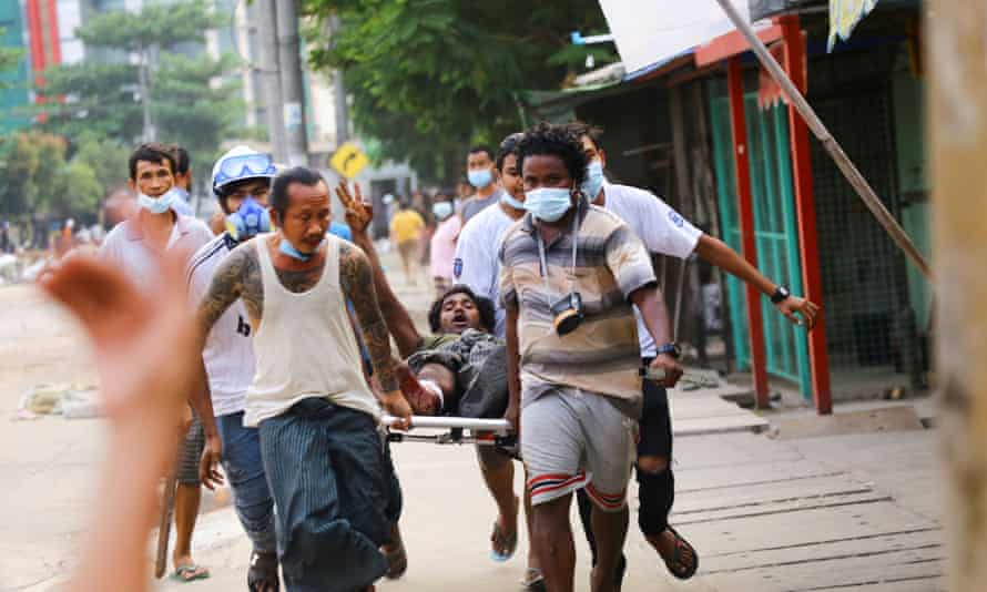 A man who was shot during the security force crackdown on anti-coup protesters shows a three-finger salute as he is helped to safety in Yangon.