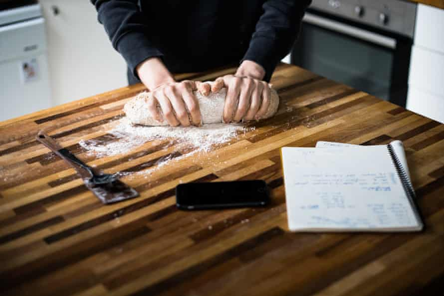 A woman kneading sourdough with a phone and a notebook