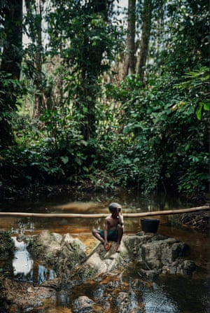 Child sits on a rock in a stream