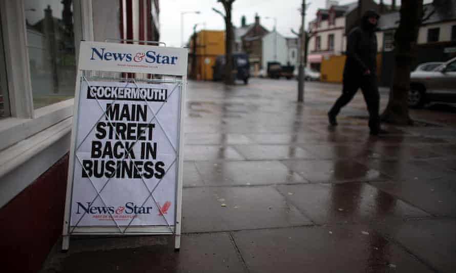 A newspaper board declares Cockermouth high street back in business after the flooding in Cumbria in 2009.