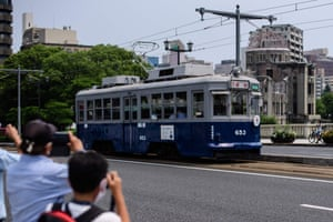 Bystanders take pictures of tram 653, which survived the atomic bombing
