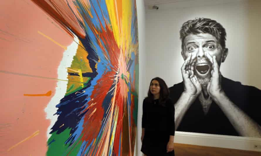 A woman looks at a painting by Damien Hirst in front of a portrait of David Bowie at Sotheby's.