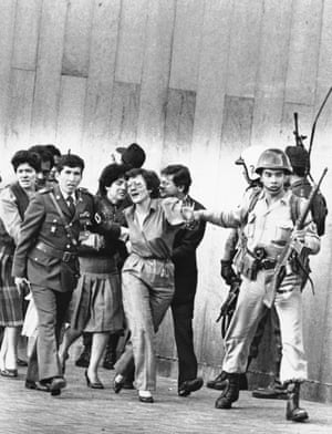 Government employees being led by soldiers and police out of the Palace of Justice in Bogotá in 1985 after an army assault on the building set free more than 100 hostages held by the M-19 guerrilla group.