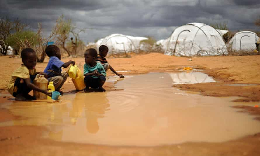 Somali boys collect water from a puddle at the sprawling Dadaab refugee complex in Kenya.