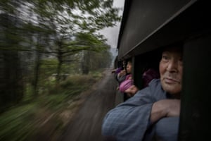 Villagers ride a local coal powered steam train at a station in the town of Shixi
