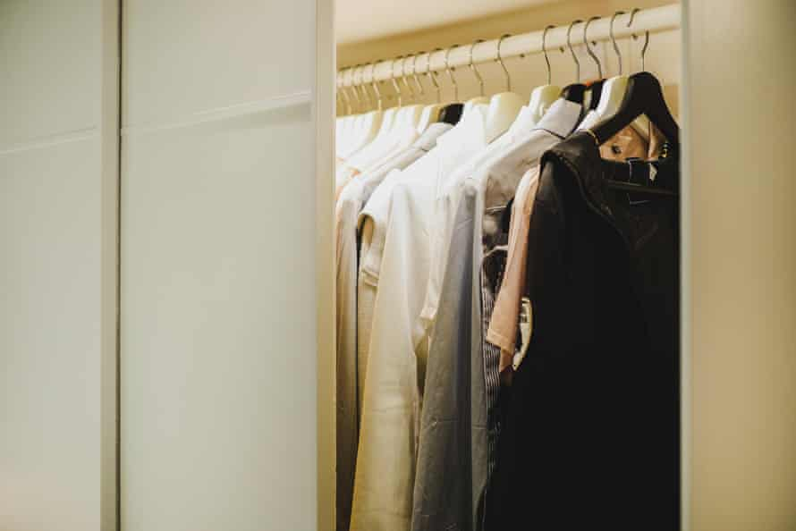 A closet with work clothes hanging in it
