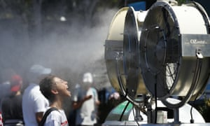 A spectator stands in front of a cooling fan spraying water at the Australian Open tennis championships in Melbourne, Australia