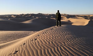 A US Border Patrol agent stands atop a dune along the US-Mexico border on 17 November 2016 near Felicity, California.