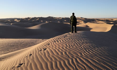 A US Border Patrol agent stands atop a dune along the US-Mexico border on 17 November 2016 near Felicity, California.