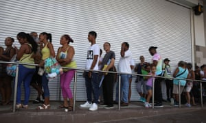 People line up to get into a Walmart store in San Juan.