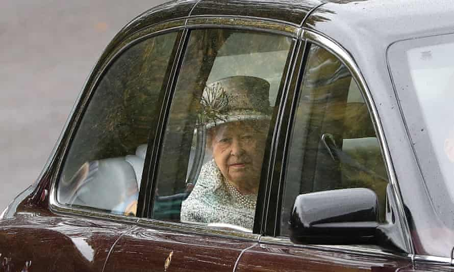 The Queen looks out the window of a car