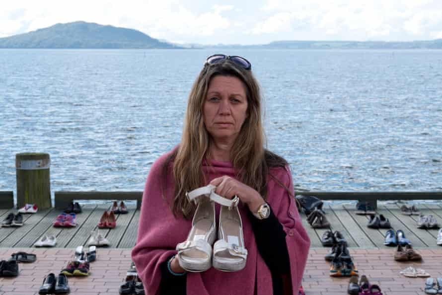 Suzy Taylor holds a pair of her daughter Georgia MacBeath's sandals in front of the shoes of other New Zealand suicide victims on the lakefront at Rotorua