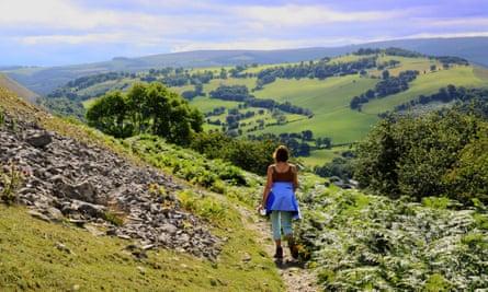 Woman walking on the Offa's Dyke long distance footpath, UK.