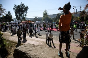 A young girl watches the procession through Gondar