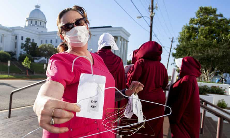 Laura Stiller hands out coat hangers as she talks about illegal abortions during a rally in Alabama.