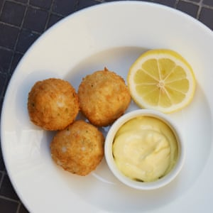 Salt Hake croquettes with half a lemon on a white plate