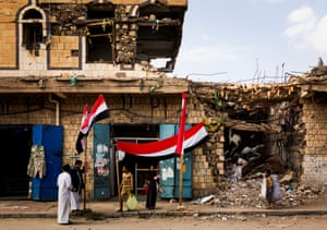 Yemeni flags in front of building bombed during coalition airstrike in Sa'dah in September