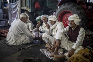Farmers huddle together as they share a hookah while blocking a major highway, at the Delhi-Uttar Pradesh state border